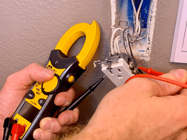 electrician testing the wiring in an outlet with a multimeter