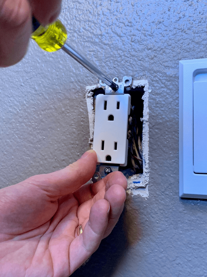 Person installing an outlet in the wall