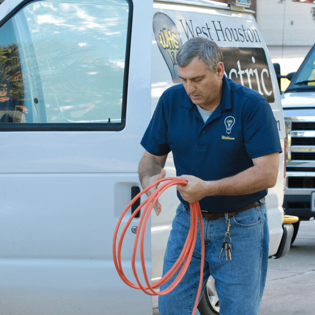 electrician gathering wires from service truck